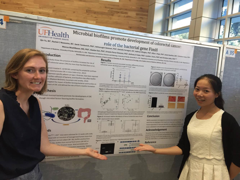 Qin Yu and Rachel Newsome show their poster on microbial biofilms and fimH